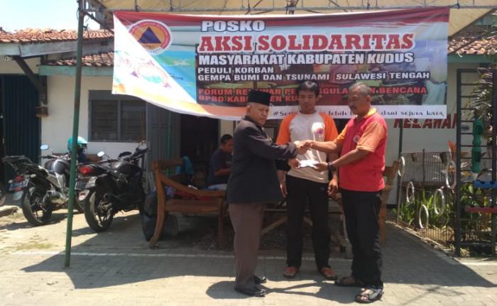 Kiai Suwantho meyerahkan donasi untuk korban gempa Palu dan Donggala di kompleks Kantor BPBD Kudus.
